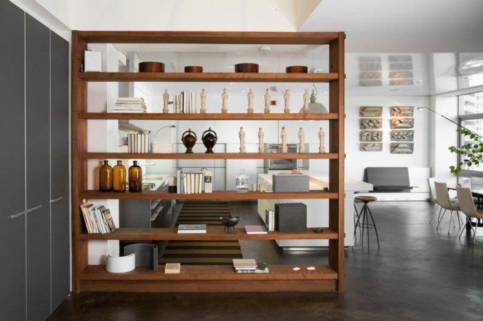 Хороший вариант зонировать пространство с помощью деревянного шкафа с полками.