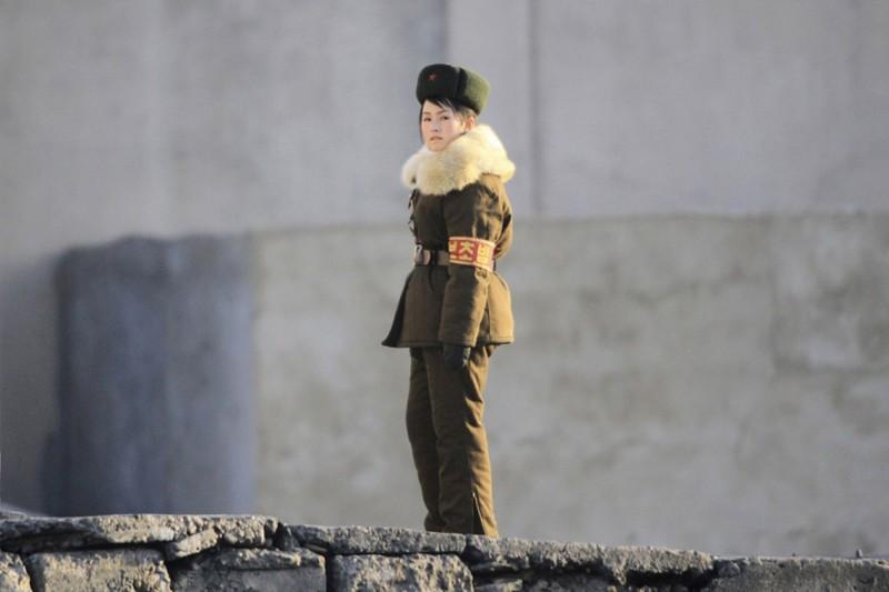 14. Пограничница стоит на страже на берегу реки Ялу, 23 ноября 2010. (Фото Jacky Chen | Reuters): Тоталитаризм, гранциа, китай, севераня корея