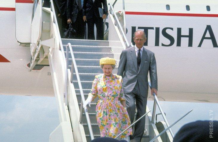 Королева Елизавета II и принц Филипп выходят из самолета.