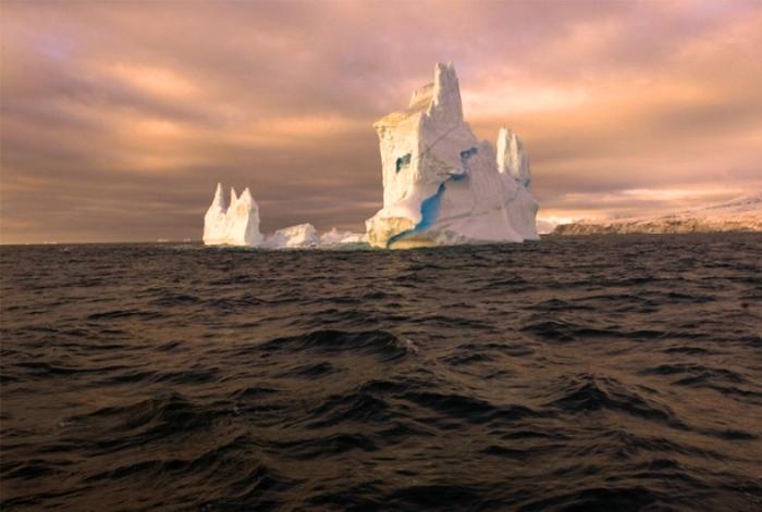 Айсберг в золотых лучах солнца.