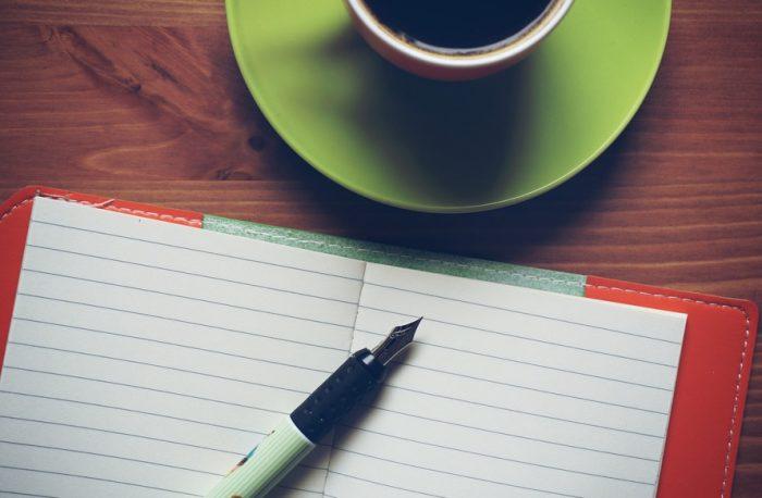 блокнот, чашка и ручка на столе