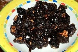 Нафаршировать грецким орехом. Если салат подается порционно, отложить по количеству порций нафаршированные ягоды. Можно заменить их на маслины.