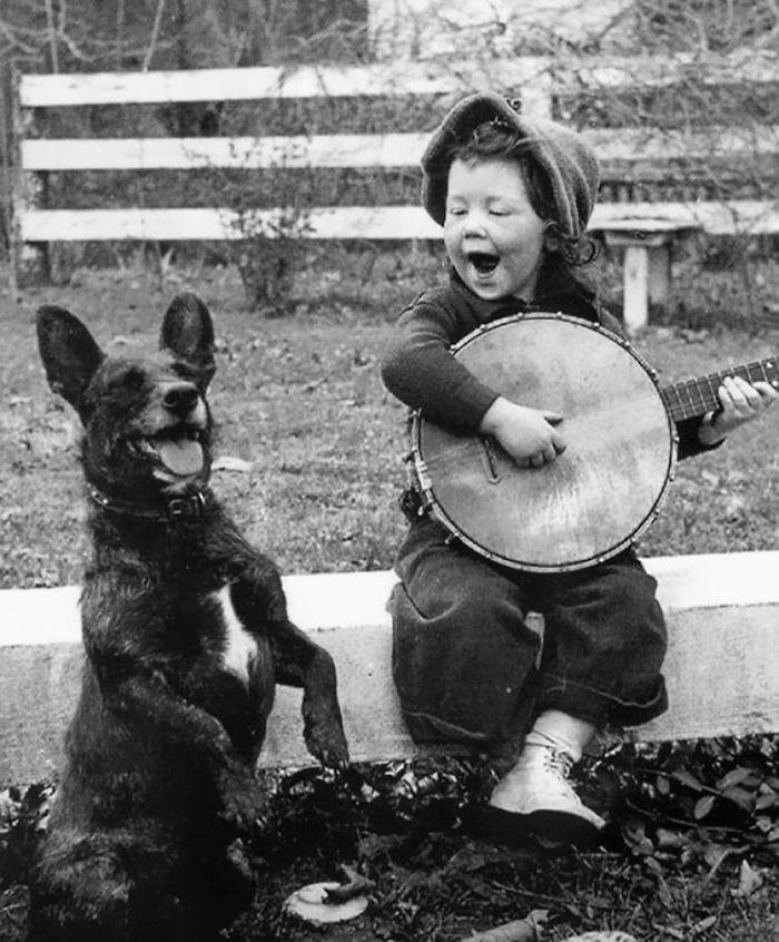 1. Девочка играет для своей собаки  детство, прошлое, фотография