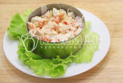 Заправить салат и выложить на блюдо с листьями салата в сервировочном кольце.