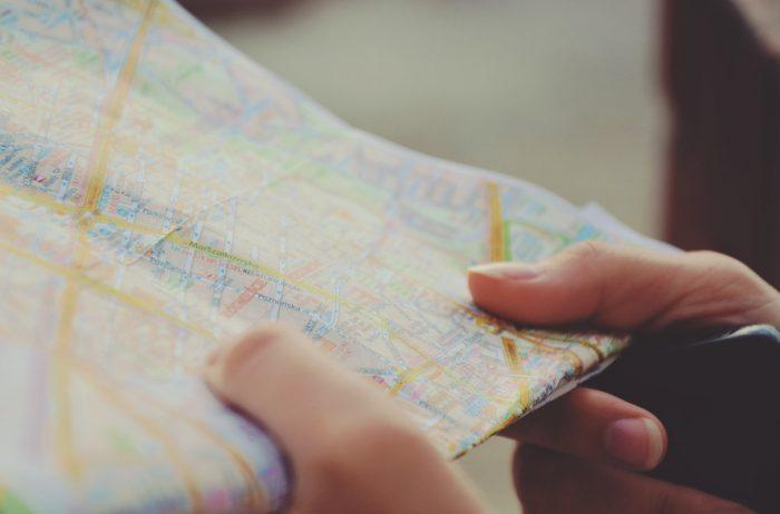 руки держат карту города