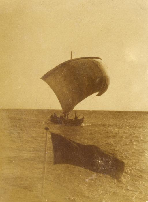 Лодка, плывущая под парусом.