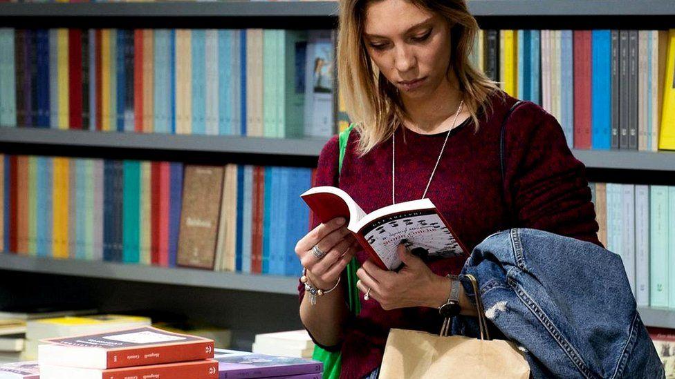 Девушка листает книгу