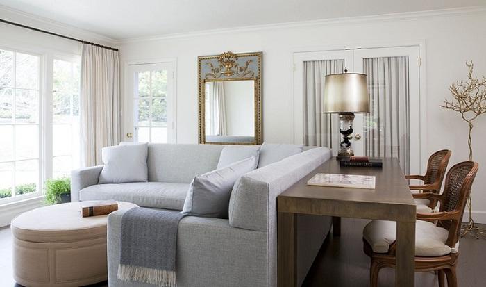 Изящный контраст между светло-серым диваном и деревянным столом со стульями.
