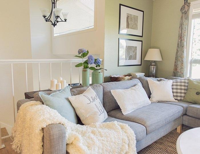 Красивый интерьер гостиной дополняют свечи и цветы, которые являются отличным украшением.