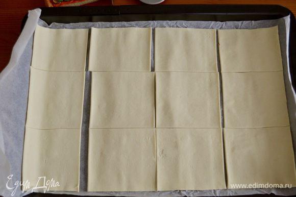 Готовое слоеное тесто развернуть и выложить на противень вместе с пекарской бумагой. Разрезать на квадраты со стороной 10 см.