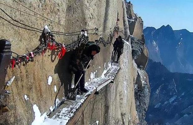 Китайские дворники чистят от снега горную тропку на высоте 700 метров
