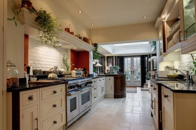 Широкая кухня в коридоре загородного дома с духовкой и посудомоечной машиной