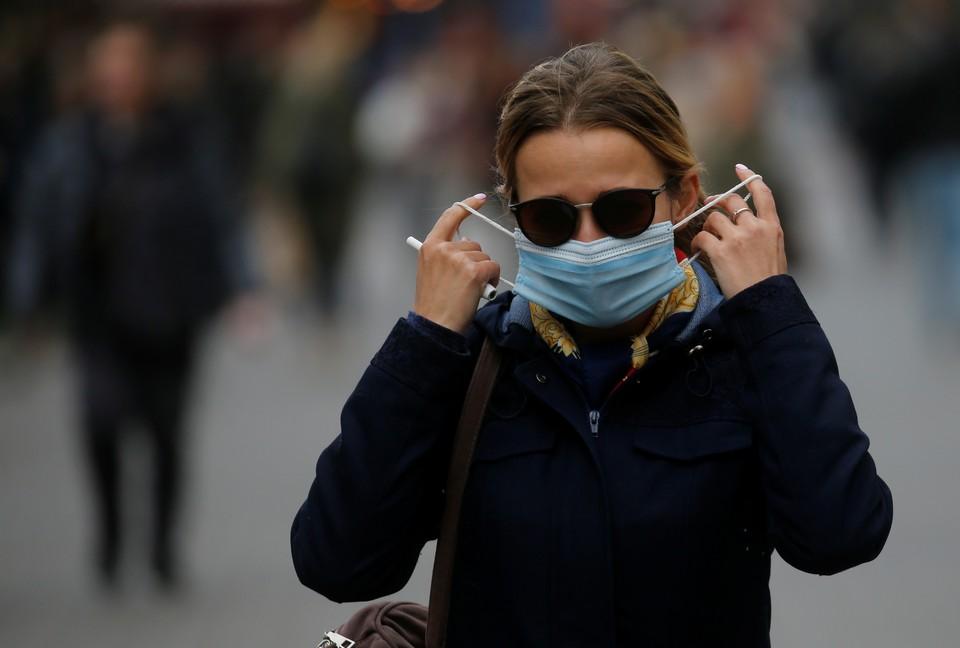Женщина в маске на улице в Киеве.