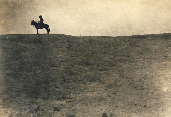 Одинокий всадник далеко в пустыне.