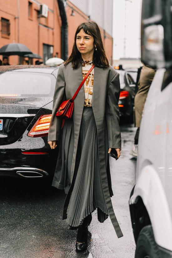 Девушка в плиссированной юбке, серый плащ и красная сумочка