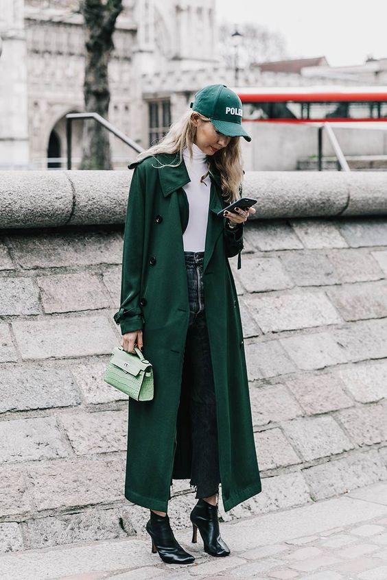 Девушка в длинном зеленом плаще, черные ботильоны, белая водолазка и бейсболка