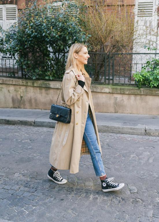 Девушка в голубых джинсах, черные кеды и сумочка, бежевый плащ