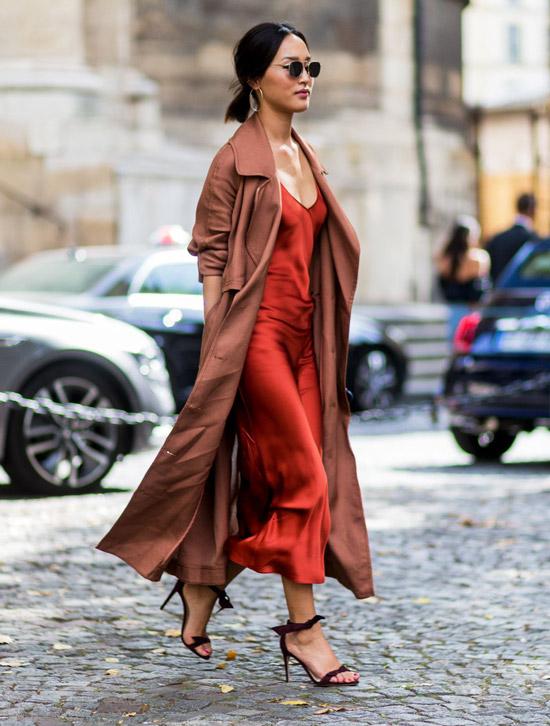 Девушка в красном платье слип, коричневом длинном плаще и босоножках на шпильке