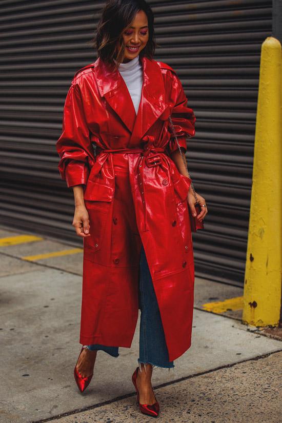 Девушка в красном лакированном плаще с поясом, укороченные джинсы и красные туфли