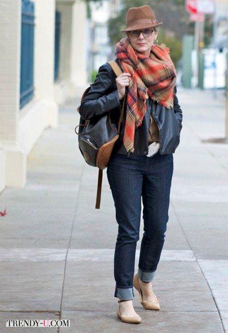 Кожаная куртка, джинсы и клетчатый шарф на женщине 60-ти лет