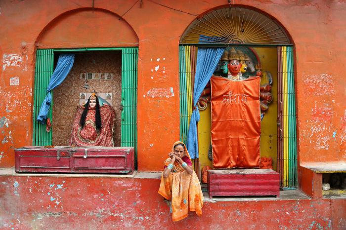 Женщина сидит возле храма почитания индийских божеств.