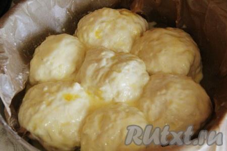 Из теста сформировать шарики и выложить их в форму на небольшом расстоянии друг от друга. Смазать тесто взбитым желтком с молоком. Оставить шарики из теста на расстойке, пока они не увеличатся в размерах.