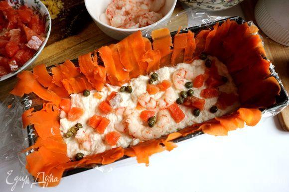 Нижний слой — часть измельченной в блендере трески, которую следует выложить равномерно на дно формы. Затем — кусочки красной рыбы, часть креветок, несколько каперсов, вяленые в масле помидоры, часть цедры, измельченной крупно.
