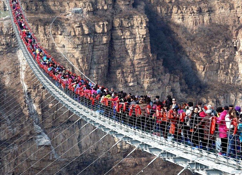 Сотни бесстрашных туристов столпились на самом длинном стеклянном мосту в мире