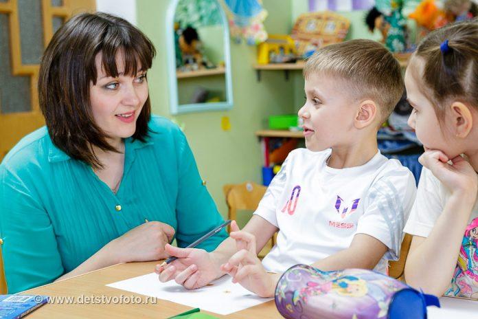 Воспитательница в детском саду помогает пацану натянуть ботинки....