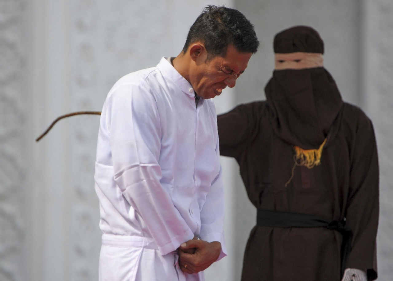 Jono Simbolon (front), an Indonesian Christian, grimaces in pain as he is flogged in front of a crowd outside a mosque in Banda Aceh, Aceh province, on January 19, 2018. Simbolon was publicly flogged on January 19 for selling alcohol in conservative Aceh province, a violation of Islamic law, as a crowd of onlookers including children jeered