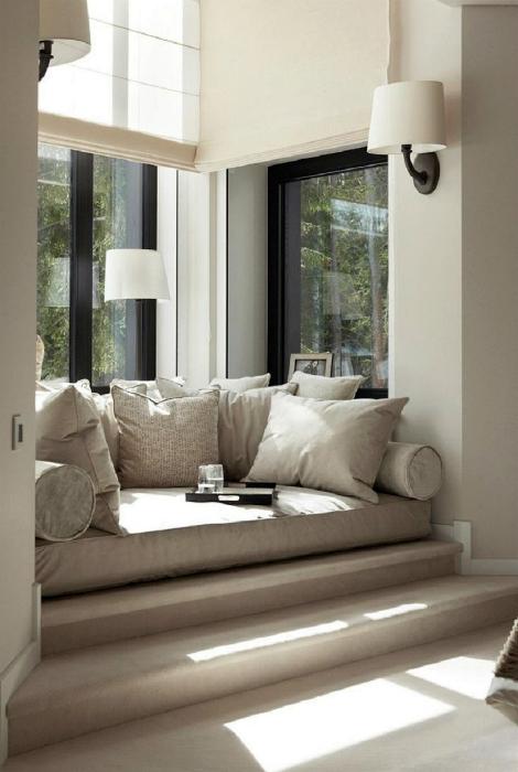 Мягкий диванчик на ступеньках у окна.
