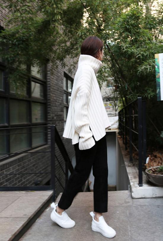 Девушка в черных брюках, белый свитер оверсайх и белые кроссовки