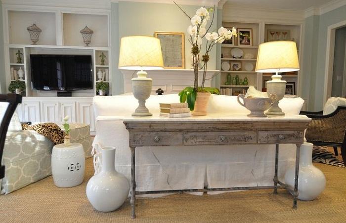 Ретро-столик на фоне светлого дивана смотрится просто и лаконично, что позволяет создать интересное и простое настроение.