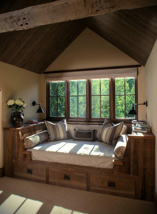 Деревянный диванчик у окна.