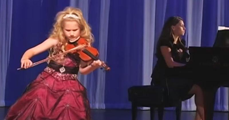 Девочка вышла на сцену со скрипкой. Когда она заиграла, в зале воцарило полное молчание