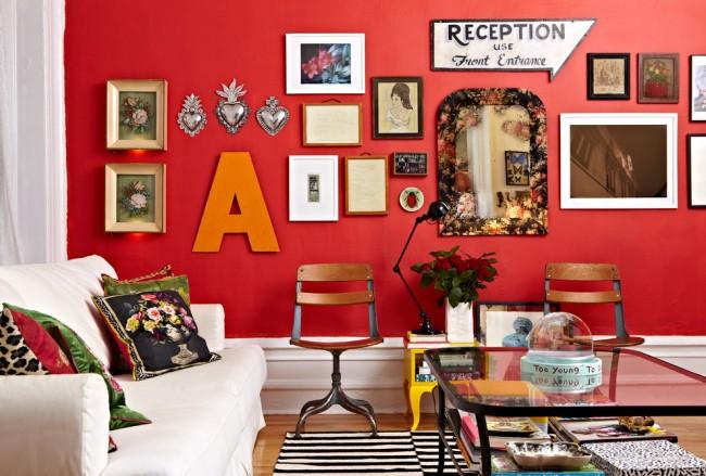 Старинные сувениры и современные картины на ярко-красной стене комнаты в богемном стиле
