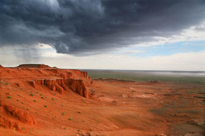 Грозные тучи, собирающиеся над красной горой в Монголии.