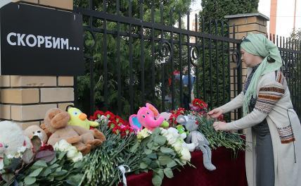 На фото: местная жительница возлагает цветы у школы № 175, где в результате стрельбы погибли люди