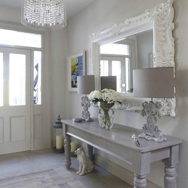 Прихожая в стиле шебби шик с красивой резной оправой зеркала и старинным узким столиком
