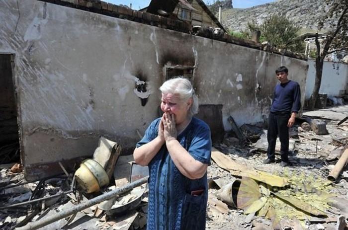 Женщина плачет у своего сгоревшего дома.