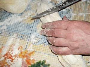 Начинаем «лепить» домашние булочки. Выкладываем тесто на стол или специальную доску, хорошенько разомнем его и разделим на несколько небольших частей – так будет удобней с ним работать.  Берем отдельно взятый кусок теста и раскатываем его в «колбаску», которую затем порежем на небольшие части. Каждая часть – это без пяти минут булочка.
