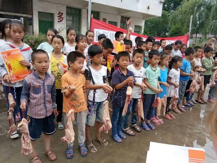 Лучшим школьникам из китайской деревни подарили по килограмму свинины