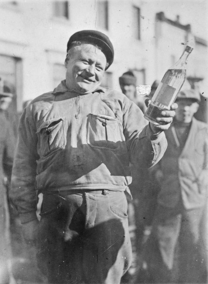 Финский кузнец Пирттимяки с бутылкой водки, которую он получил в подарок после того как отстоял в очереди всю ночь и стал первым покупателем магазина Alko после отмены сухого закона. Финляндская Республика. 5 апреля 1932 года. история, люди, мир, фото