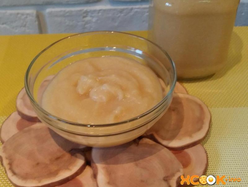 яблочное пюре в стеклянной пиале на подставке из дерева на столе, застеленном желтой скатертью