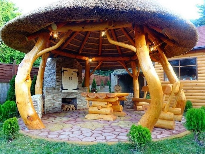 Интересная идея перголы в виде гриба, сделанная из дерева.