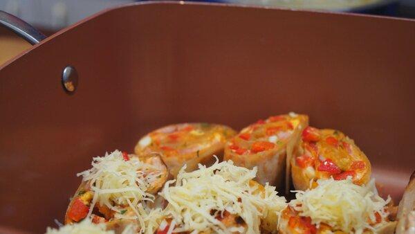 Нарезанные рулетики выкладываем на разогретой сковородке, обжариваем с двух сторон по 2-3 минуты. Затем посыпаем сыром и закрываем на 7-10 минут крышкой