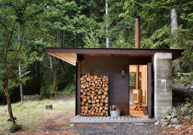 Небольшая летняя кухня на территории двора частного дома с отведенным местом под навесом для поленницы для дров