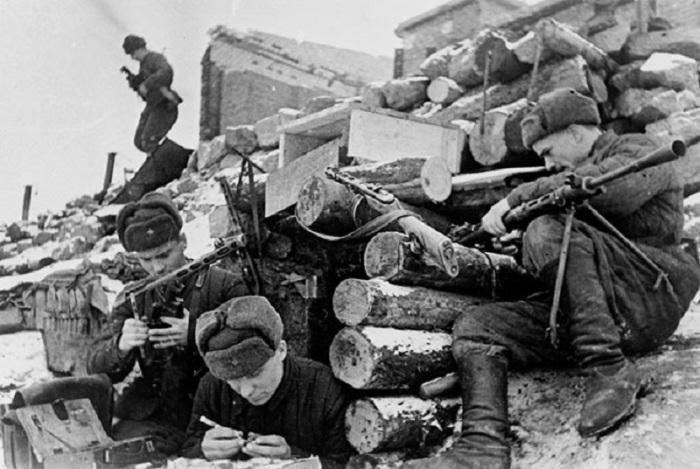 Красноармейцы у землянки в Сталинграде чистят оружие.