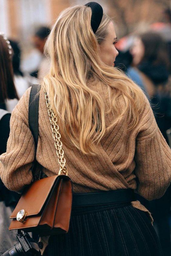Девушка в черной юбке, коричневая теплая кофта, коричневая сумка на цепном ремне и черный ободок