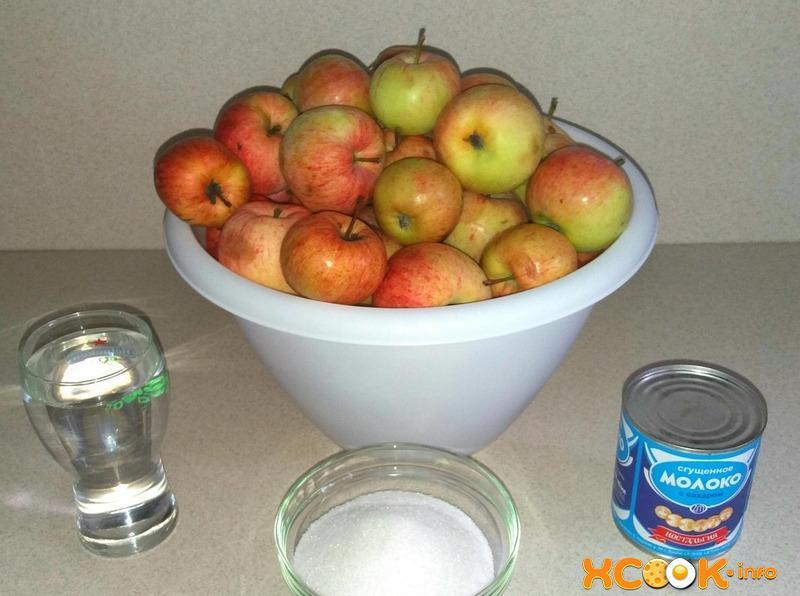 горка яблок в миске, банка сгущенки, сахар в пиале и вода в стакане на кухонном столе